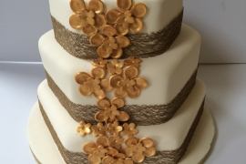 Hexagonal WEdding Cake with Burlap Ribbon and Gold Decorations